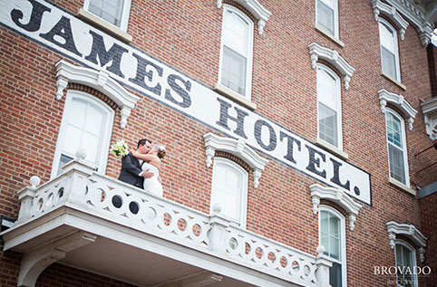 Looking up at the historical St. James hotel a new bride and groom embrace on the balcony.