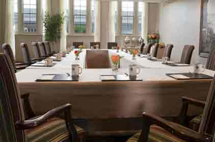 Main streeter meeting room with a conference table with 18 plush padded chairs around a table.