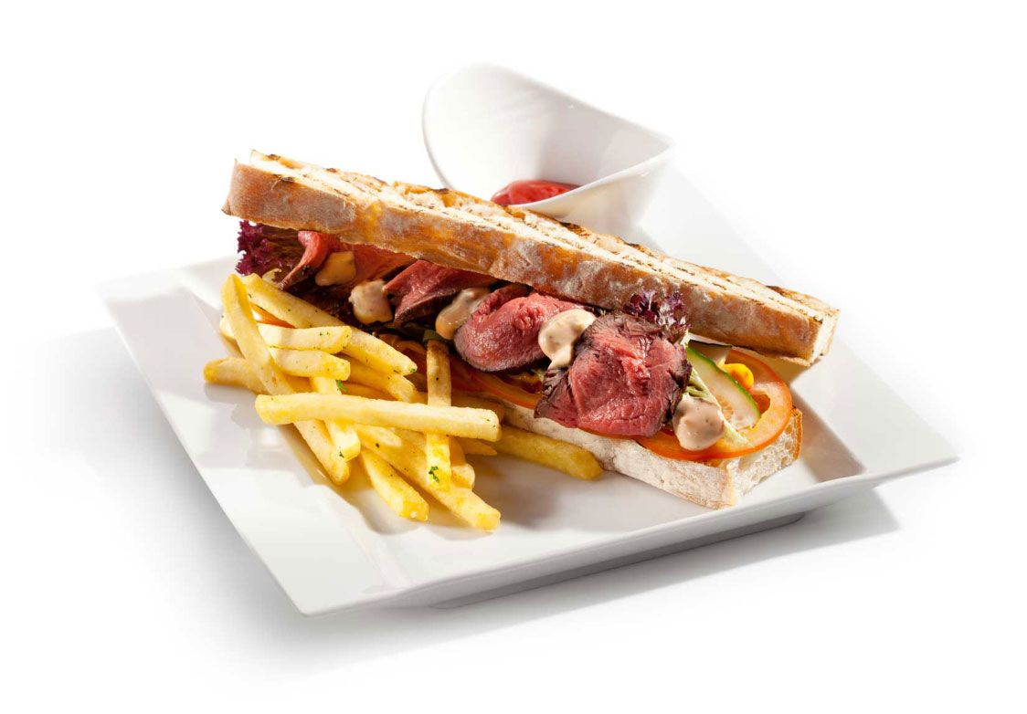 sandwich with french fries on a white plate